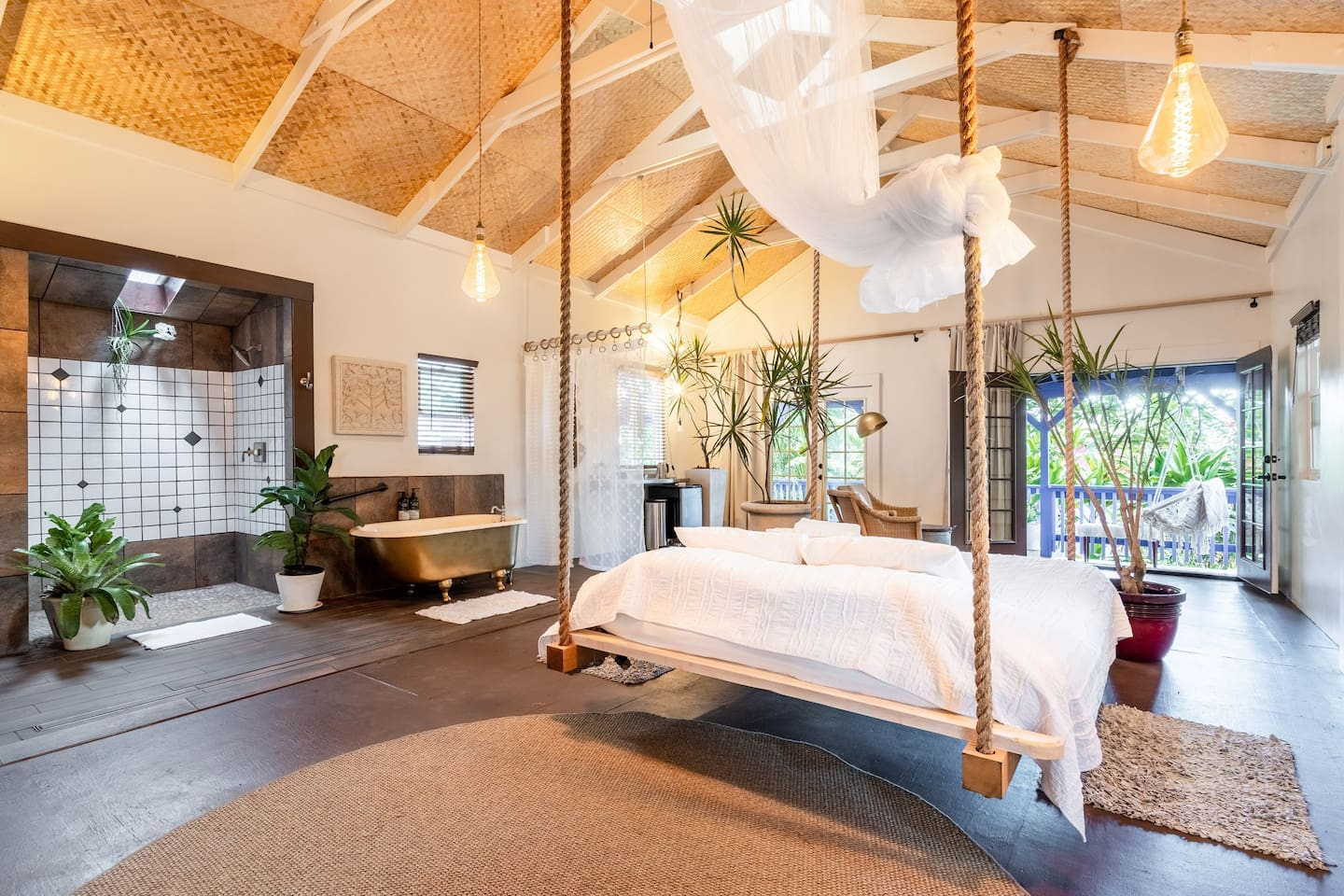 Sleep on a cloud ! This is a Cal King bed suspended from the ceiling with quality linens for a great night of rest nestled in this garden loft apartment. Clawfoot tub and light filled shower add to the options for guests to relax and unwind.