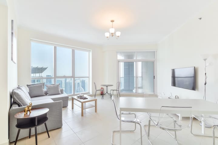 Clean and airy living room with bird's-eye views of Dubai Marina, access to a private patio, a 6-person dining area, a cozy rest area and a 55 inch Smart TV and 250 MB high speed internet