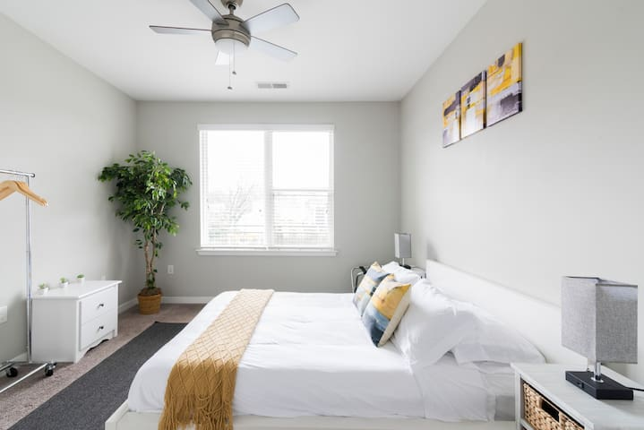 Cozy duvet covers on a queen bed, woven quilts, and warm lighting are how we ensure that guests always feel at home in our apartment.