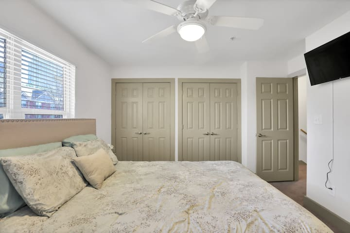 Master bedroom with tv on the wall and connecting bathroom.