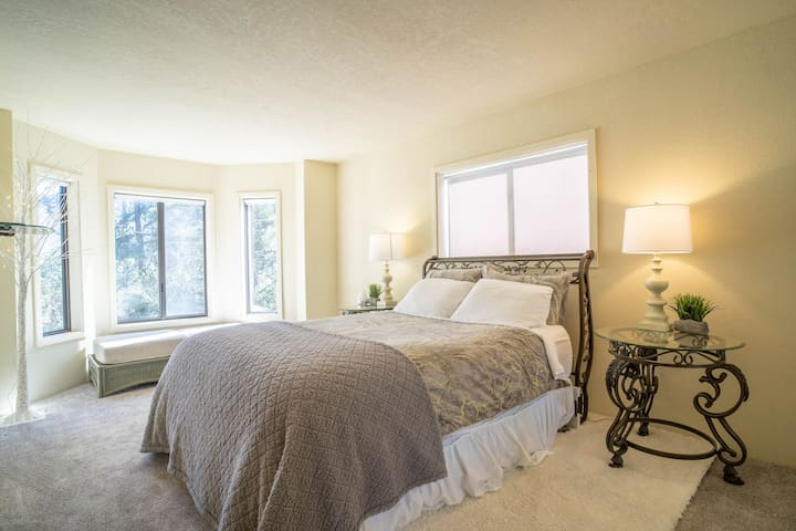 Large Master bedroom with forest views from the bed.