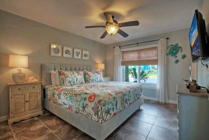 Master suite offers king size bed and flat screen TV; ensuite bathroom with closet.