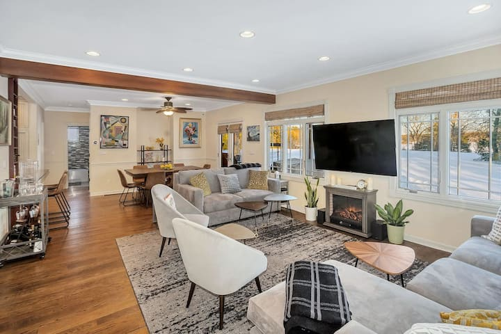 """Living room with fireplace, 55"""" smart TV, queen+ pullout sofa, and picturesque view of the lake"""