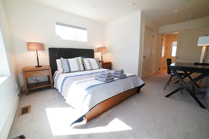 The master bedroom comes with a queen bed, a full bath, and a lovely desk for reading or work.