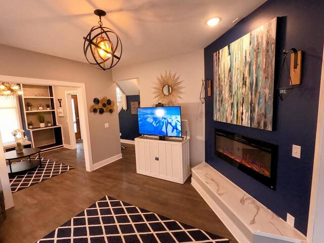 """The living room has a 60"""" fireplace, large hearth and TV credenza. With the push of a button the TV is either hidden for peace and quite or revealed for entertainment."""
