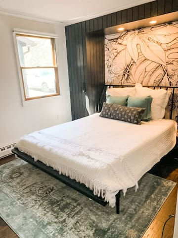 Medium bedroom with queen bed and accent wall