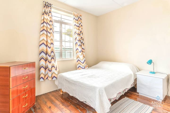Bedroom with a double bed, also spacious w/ a dresser for your things.