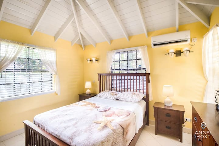 Bedroom with plush queen-sized bed, tropical decor & high ceilings.