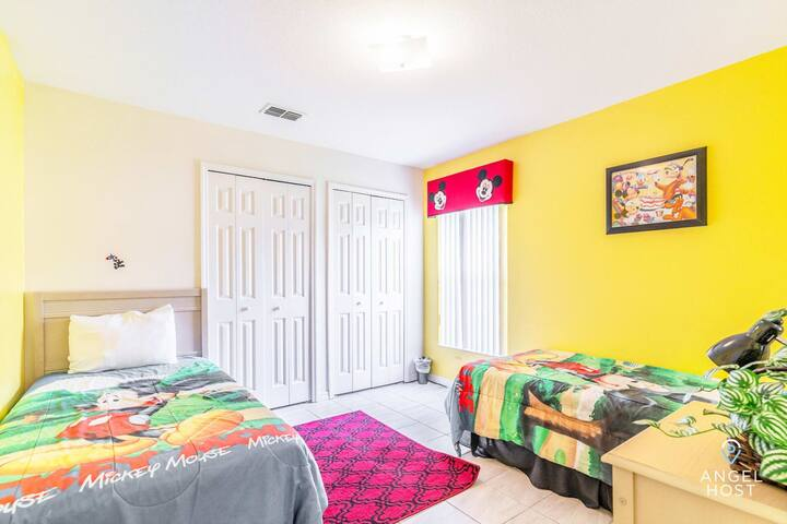 Bedroom 5 is a yellow cheerful Mickey Mouse room w/ two twin beds.