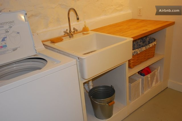 ... room with washer and dryer, iron, ironing board and utility sink